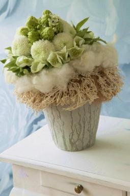 Kytice je svázána z vybledlého roští, hrubé bavlny, čemeřic, chryzantém a snědků.