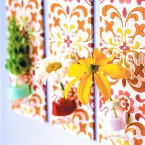 Stěnu ozdobí květiny v plastových kalíšcích na pozadí staré tapety.