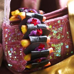 Kabelku zdobí svitky listů Cordyline, plátky pryšců, karafiátů a žlutých růží.