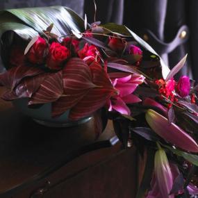 Červené lilie a růže, pryšce a pryskyřníky tvoří skutečný květinový vodopád.