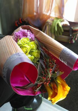 Aranžmá kal, pryšců, karafiátů a smetanových růží spojené pruhem balicího papíru.
