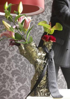 Lilie a květ anturie vykukuje z vázy ovázané kravatou.