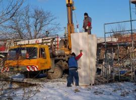 Foto: www.uspornedomy.cz, Panely na kamiony nebyly správně naloženy – před vyložením obvodových stěn bylo nutné vyskládat menší příčky.