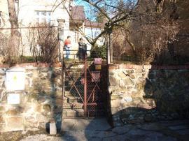 Foto: ČESKÉSTAVBY.cz, zpevnění svahu kamennou zídkou a původní oplocení v dolní části pozemku