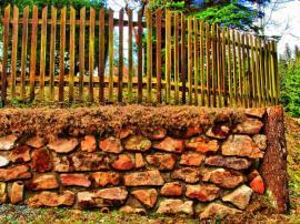 Ilustrační foto (www.shutterstock.com), Zpevnění svahu kamennou zídkou ukončené dřevěným špalkem + dřevěný plaňkový plot