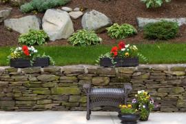 Ilustrační foto (www.shutterstock.com), kamenná zídka zpevňující svah, kde je čerstvě založená skalka doplněna velkými kamennými solitéry i menšími kameny