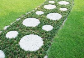 Ilustrační foto (www.shutterstock.com), zajímavé řešení - cestu s odlišným druhem trávy s tmavším listem, než jakou najdeme na okolních travních plochách, lemují kameny a v její ploše jsou položené plastové kruhové šlapáky (nebo je to beton?)