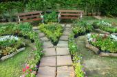 Ilustrační foto (www.shutterstock.com), zajímavé řešení z opracovaných kamenných čtverců pro náročné, květinové záhonky pro změnu lemuje dřevěná kulatina zbavená kůry