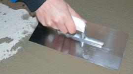 Uhlazení povrchu betonu pomocí nerez hladítka.