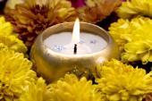Svíčka obklopená květy chryzantém