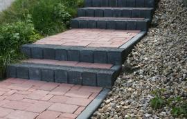 Betonové obrubníky + palisády, které vytvářejí společně se zámkovou dlažbou schody, řešící svažitost pozemku
