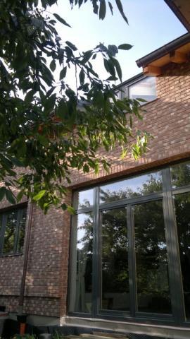 Detail fasády z lícových cihel a oken realizovaného RD, v popředí bude ještě přistavěna zimní zahrada