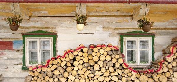 Skladované suché dřevo u stěny staré chalupy - pod převisem střechy