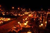 Hřbitovy žijí o dušičkách i v noci - světlem a aranžovanou krásou v kontrastu s opracovaným přírodním kamenem a tradičními náboženskými symboly