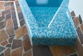 Vytápěná podlaha s kamennou dlažbou okolo interiérového bazénu