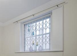 Nůžkové mříže instalované z interiérové strany okna, ve středu je patrný zámek