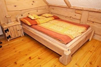 Dřevěný interiér doplňuje vtipně řešená masivní dřevěná postel