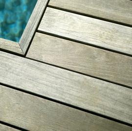 Dřevěná terasa z exotické dřeviny kolem bazénu, viditelná šeď je běžnou patinou