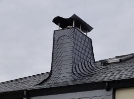 Speciální použití břidlice - opláštění komína navazuje na střešní krytinu, prostup střechou je tak vyřešen jen s pomocí břidlice