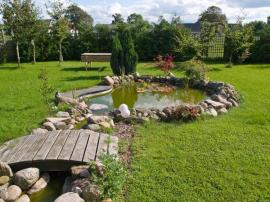 Zahrada s převažujícím travním porostem, geometricky jí dominuje jezírko s přitokem vody a můstkem