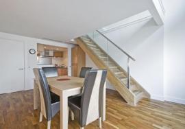 Masivní stůl, čalouněné židle a schodiště