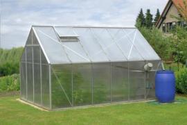 Umístění skleníku na volném prostranství zahrady obehnané dřevinami - větrolamy