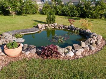 Zahradní jezírko oddělené malou kamennou hrází, terasová prkna jsou protiskluzná