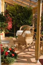 Zahradní pergola a ratanové křeslo