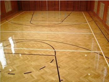 Tradiční lakovaná parketová podlaha v tělocvičně