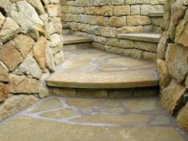 Kamená dlažba a schodiště uprostřed kamenných opěrných zídek