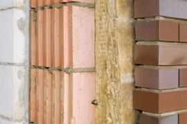 Tepelná izolace vložená mezi nosné zdivo z keramických tvarovek a obklad z lícových cihel
