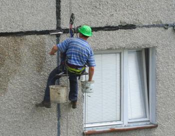 Vymazávání spár a trhlin ve stěnách panelového domu