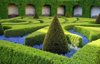 Tento tvarovaný živý plot neohraničuje prostor, ale vytváří obrazce v něm v kombinaci s květinami
