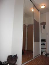 Skříň s botníkem a věšákovou stěnou umístěná v úzké chodbě panelákového bytu. Vyrobená v bílém dekoru plynule navazující na zeď. Zrcadlo přes celou plochu dveří prostor ještě dále zvětšuje.
