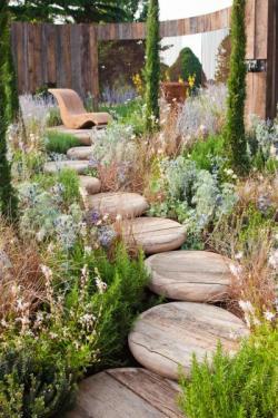 Úchvatně řešený přístup k posezení ve svažité zahradě - základním materiálem je zde dřevo