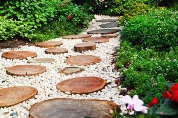 Kombinaci oblázků a do země usazených dřevěných kulánů - ideální je v tomto případě tvrdé dřevo, například dub či modřín