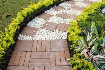 Kombinace drážkovaných přířezků z terasových prken a oblázků, chodník volně navazuje na terasu
