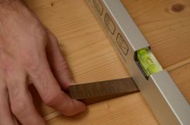 Ověřování rovinnosti se měří pomocí dvoumetrové latě a klínku pro určení míry průhybu