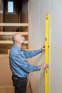 Dvoumetrovou latí inspektor přeměří rovinnost všech povrchů bytu
