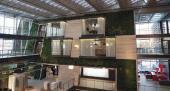 V jedné z kancelářských budov se nachází zelená stěna modulového systému pod úhlem. Atrium poskytuje dostatek denního světla, což snižuje náklady na umělé osvětlení, zdroj: Image Courtesy © William McDonough + Partners