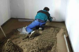 Stahujeme nasypaný beton v požadované výšce, čím dáme základ betonové podlaze.